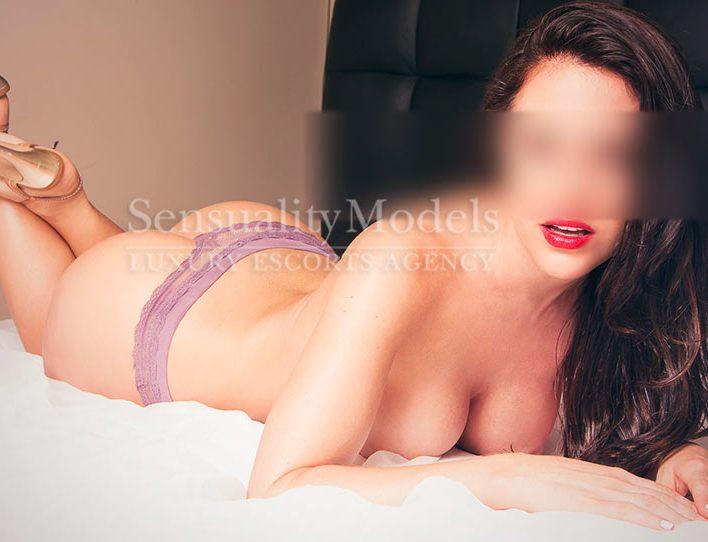Carina bella escort de lujo tumbada en la cama en topless
