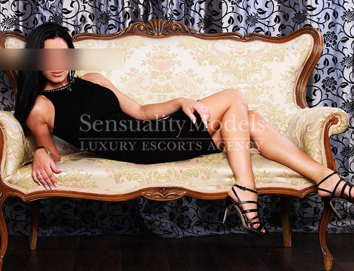 top model vestido negro en un sofá
