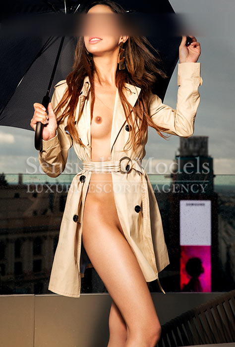 chanel semidesnuda con paraguas y gabardina desabotonada
