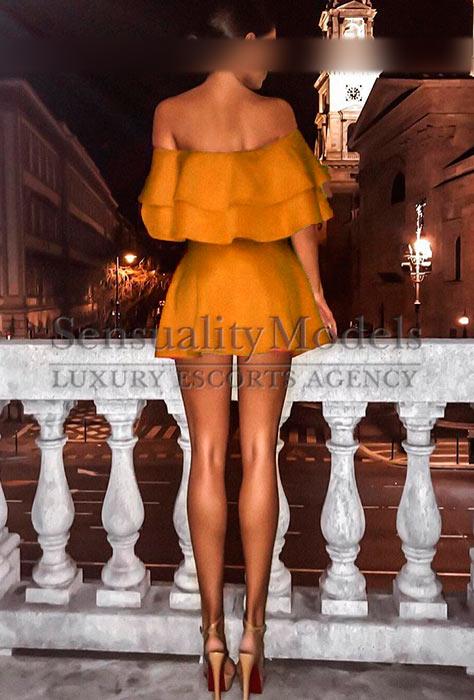 modelo con un conjunto de blusa y falda mostrando sus largas piernas