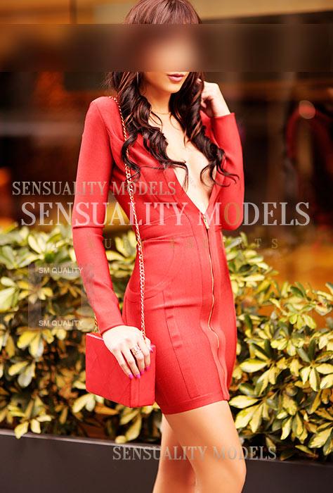 Rubi modelo con un vestido rojo y un bolso a juego