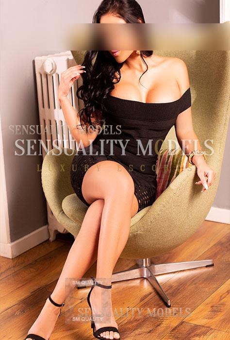 Modelo sexy sentada en sofa