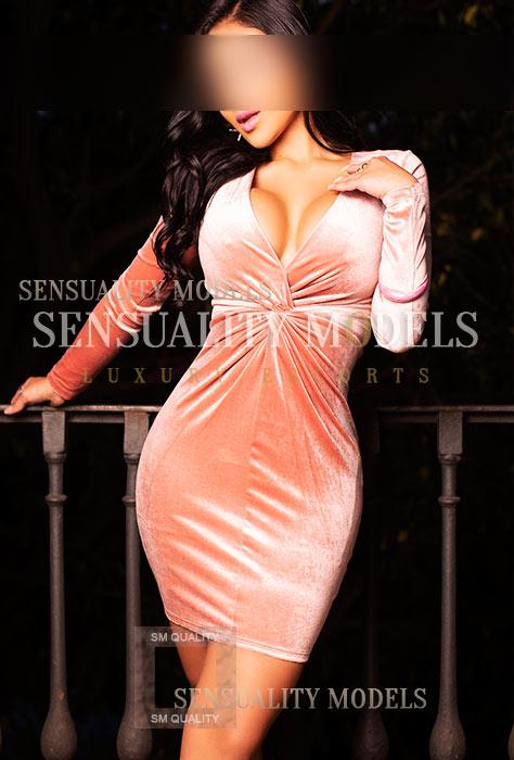 Angélica con un vestido color champagne y grandes pechos